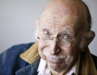 Portrait of a senior citizen wearing glasses and a jean jacket in a studio. _8401036.jpg